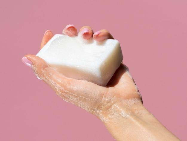 Mão segurando a barra de sabão com espuma