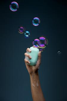 Mão segurando a barra de sabão e bolhas, vitória contra o conceito de coronavírus