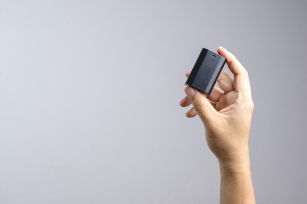 Mão segurando a bateria da câmera