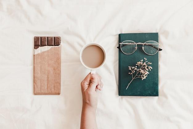 Mão segurando a bebida quente perto de livro e chocolate no lençol