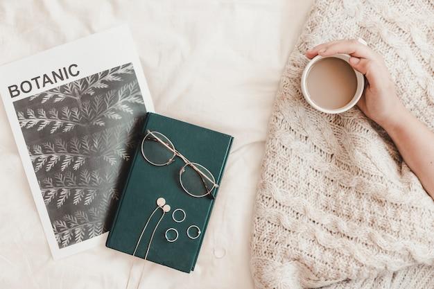 Mão segurando a bebida quente perto de óculos de livro e banner