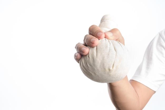 Mão segurando a bola de compressa herbal tailandesa para massagem terapêutica