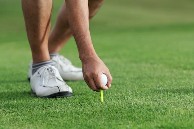 Mão segurando a bola de golfe com o tee no campo