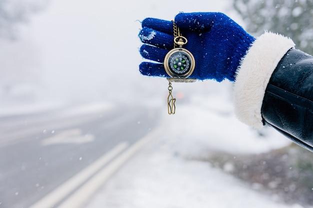 Mão segurando a bússola dourada em uma estrada paisagem de neve.