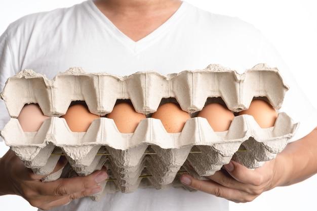 Mão segurando a caixa de ovos de galinha fresca