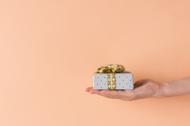 Mão segurando a caixa de presente pequena