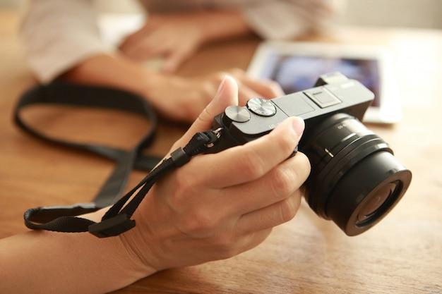 Mão segurando a câmera com mostrando a tela traseira na mesa de madeira