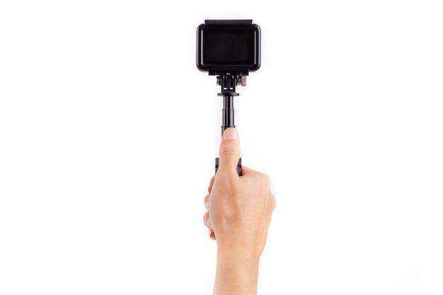 Mão segurando a câmera de ação no estabilizador isolado no fundo branco