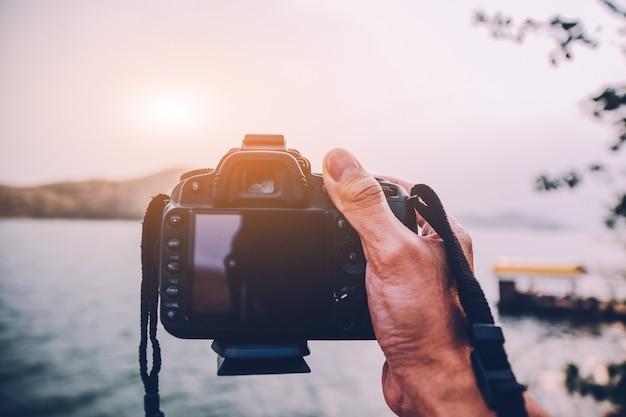 Mão segurando a câmera dslr para viajar ao pôr do sol no rio, vintage de viagens de férias