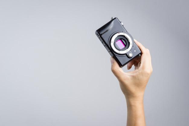 Mão segurando a câmera sem espelho com sensor micro 4/3