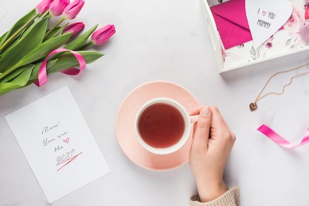 Mão segurando a caneca de chá vista superior