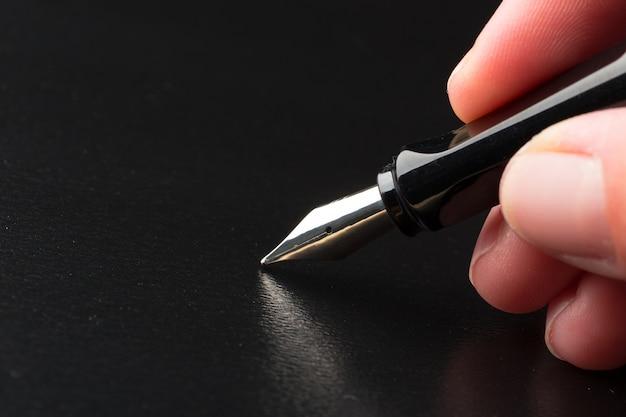 Mão segurando a caneta-tinteiro