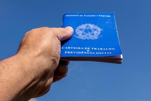 Mão segurando a carteira de trabalho brasileira apontando para o céu. conceito de aumento de salário.