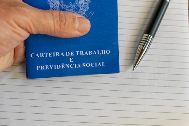 Mão segurando a carteira de trabalho brasileira com caneta e fundo branco.