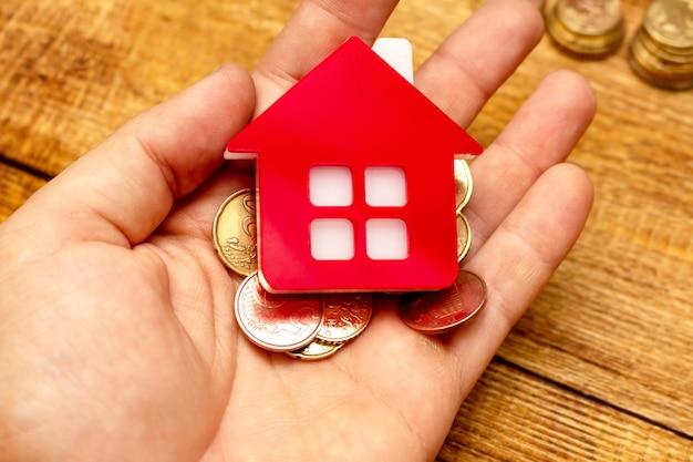 Mão segurando a casa em casa e o conceito imobiliário de dinheiro