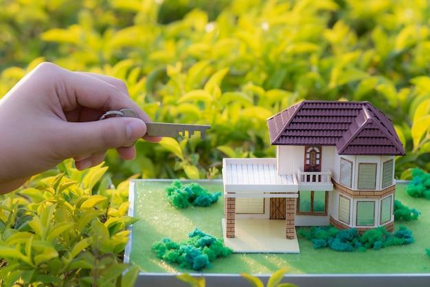 Mão segurando a casa modelo e chaves