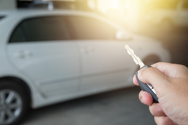 Mão segurando a chave do carro remoto no fundo do parque de estacionamento