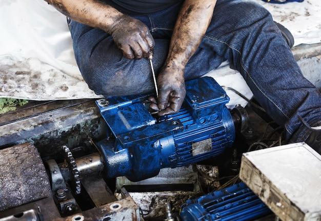 Mão segurando a chave hexagonal e durante o trabalho de manutenção do motor elétrico
