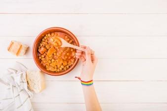 Mão segurando a colher com comida na mesa
