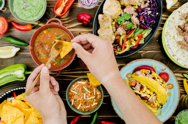 Mão segurando a colher e nacho perto de comida mexicana