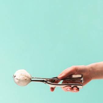 Mão segurando a colher inoxidável com saboroso sorvete de baunilha