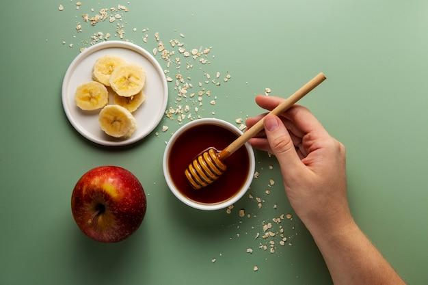 Mão segurando a concha de mel de perto