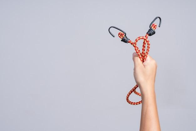 Mão segurando a corda de borracha elástica com gancho no final
