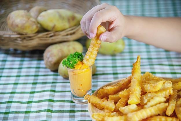 Mão segurando a deliciosa batata frita na chapa de madeira com molho