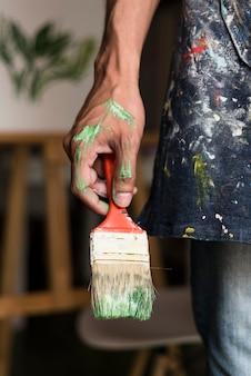 Mão segurando a escova manchada