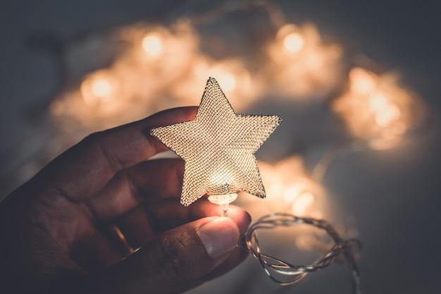 Mão segurando a estrela da lâmpada de natal no fundo branco
