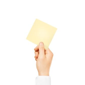 Mão segurando a etiqueta amarela quadrada em branco isolada
