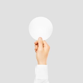 Mão segurando a etiqueta branca em branco redonda simulada acima