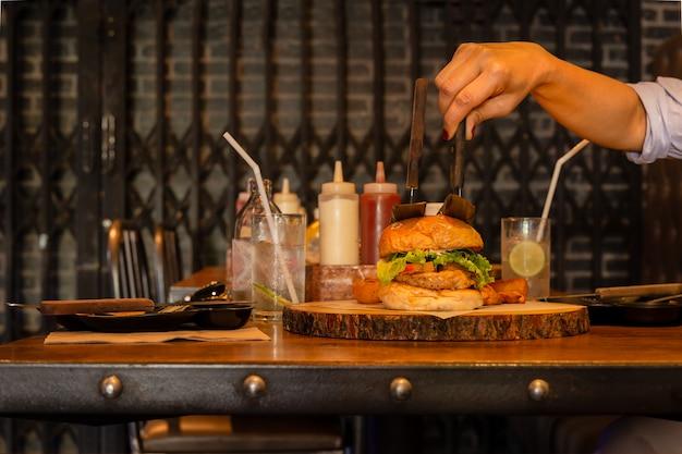 Mão segurando a faca com hambúrguer com água com gás.