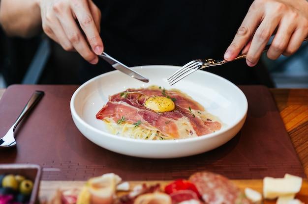 Mão segurando a faca e o garfo para comer fettuccine carbonara com presunto de parma e gema com pimenta preta.