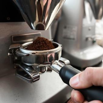 Mão segurando a ferramenta para fazer café de perto