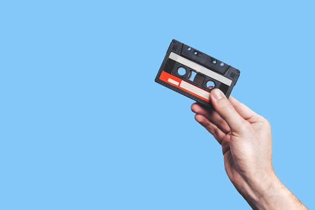 Mão segurando a fita cassete. usado fita cassete. cassete de áudio.