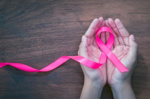 Mão segurando a fita rosa na madeira. conscientização do câncer de mama. cuidados de saúde e medicina conceito