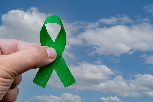 Mão segurando a fita verde para apoiar pessoas com câncer renal e problemas de saúde mental.