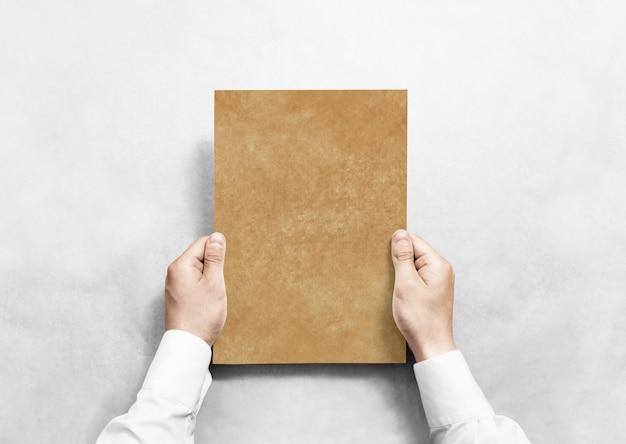Mão segurando a folha de papel em branco kraft