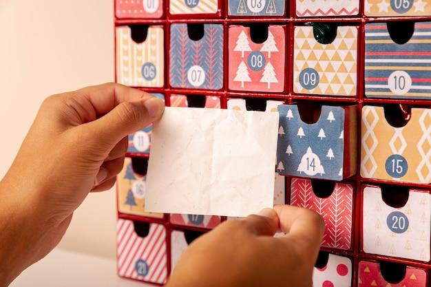 Mão segurando a folha de papel na frente do calendário do advento