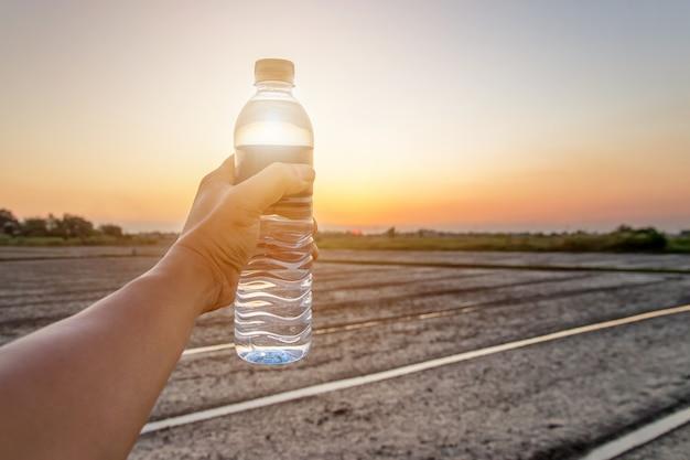 Mão segurando a garrafa de água no céu por do sol, férias de férias de verão ao ar livre e vista à noite, bebidas, pessoas e estilo de vida