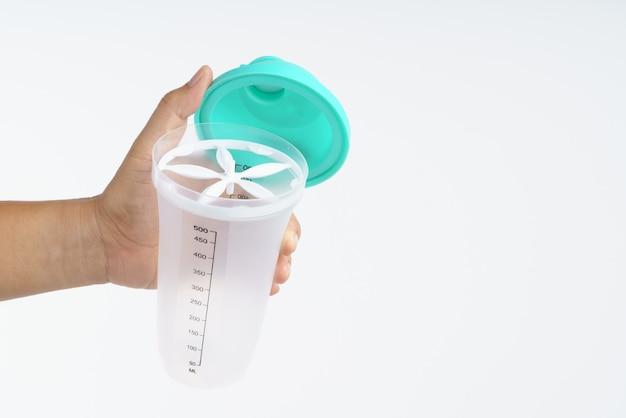 Mão segurando a garrafa de água plástica com agitador de pó para fazer bebida