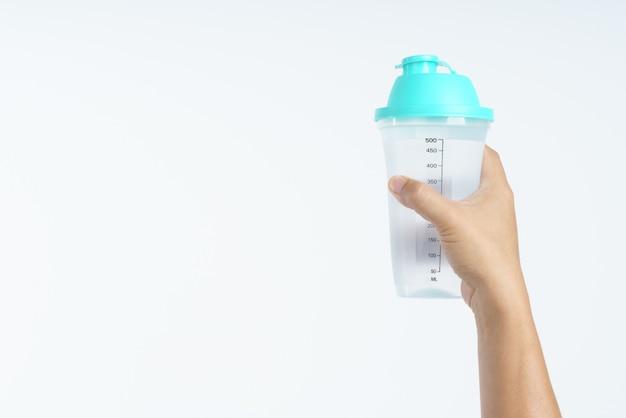 Mão segurando a garrafa de água plástica com medidor de 500 ml