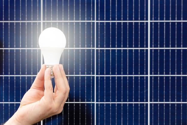 Mão segurando a lâmpada branca contra o painel solar, estação solar. conceito de ideia de energia alternativa, tecnologia, meio ambiente, ecologia. energia verde. close up com espaço de cópia.