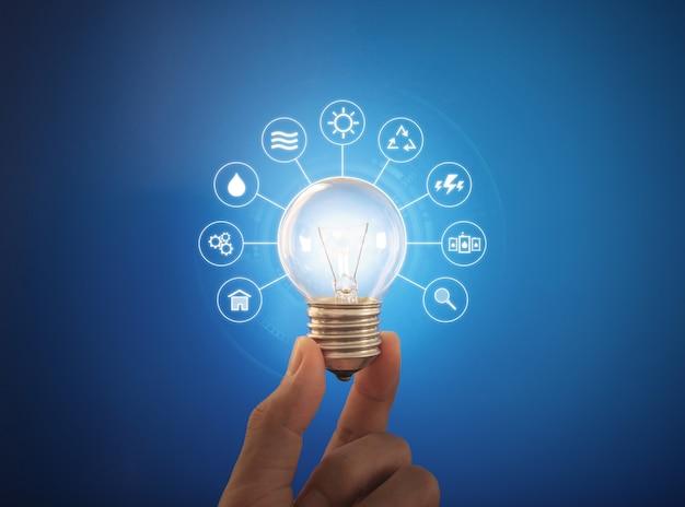 Mão segurando a lâmpada brilhante com ícone de recursos de energia, sobre fundo azul. conceito de energia