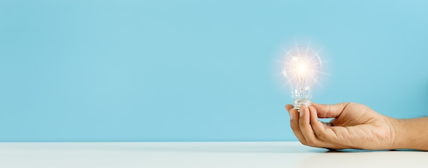 Mão segurando a lâmpada com fundo azul de reflexo de luz. símbolo de criatividade, ideias e conceitos criativos. cópia espaço banner.