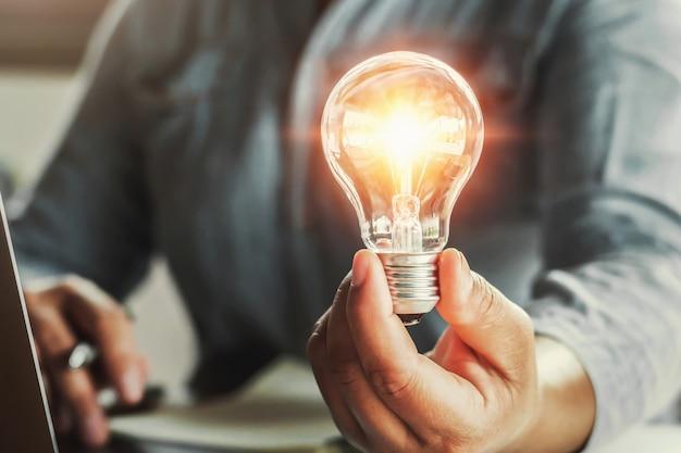 Mão segurando a lâmpada. conceito de ideia com inovação e inspiração