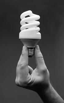Mão segurando a lâmpada em espiral