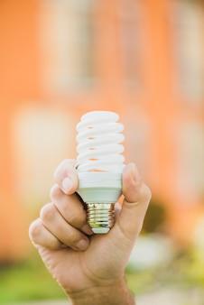 Mão segurando a lâmpada fluorescente compacta de poupança de energia ao ar livre