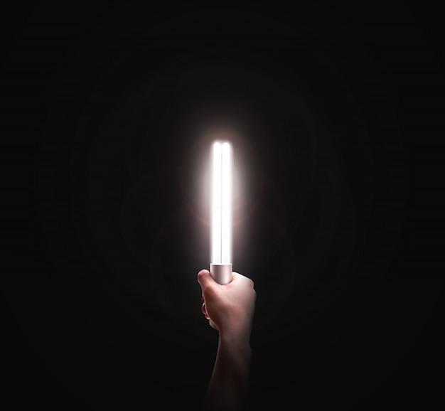 Mão segurando a lâmpada no preto